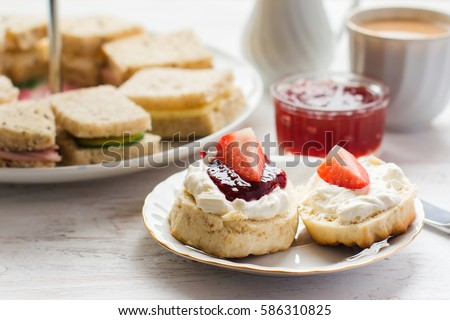 Traditional English afternoon tea: scones with clotted cream and jam, strawberries, with various sandwiches on the background, selective focus