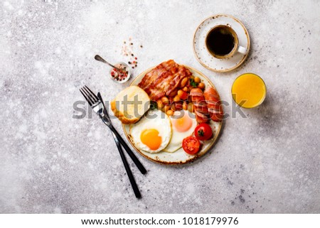 Traditional English Breakfast Food on stone Eggs ,Sausages, Bacon, Beans,Toasts,Coffe and Orange juice Top View #1018179976