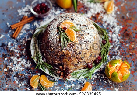 Traditional English Christmas plum pudding, sugar icing, mandarins and berries on blue background.