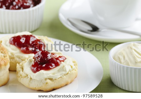 Traditional English cream tea of scones, clotted cream, strawberry jam and a cup of tea. These are served Devonshire style, with the jam on top.