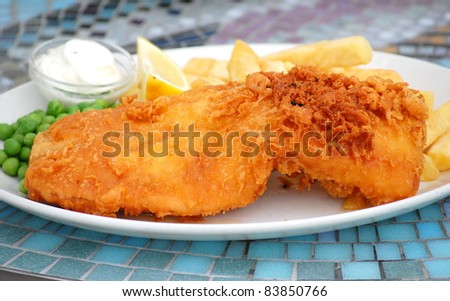 Traditional English Fish and Chips on a plate.  Battered Fish at the front.