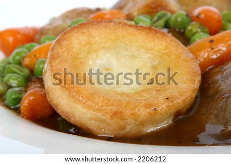 Traditional English Sunday roast with Yorkshire pudding and summer vegetables macro close up isolated on white