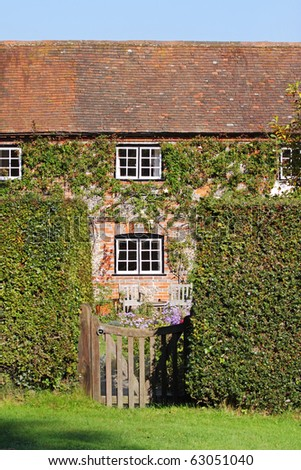 Traditional English Village Cottage and garden with Climbing plants on the Wall