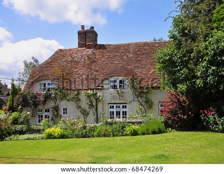 Traditional English Village Cottage and garden with Climbing roses on the Wall