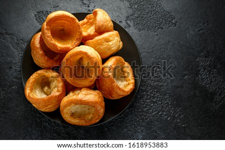 Traditional English Yorkshire pudding side dish on black plate and background Stock photo ©