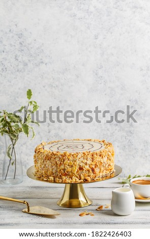 Traditional Esterhazy cake with almond on golden cake stand over white background with cup of coffee and cake spatula. Side view, copy space Foto stock ©