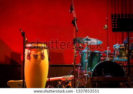 Traditional ethnic Cuban conga drum and modern drum set on red background. Percussion instruments at a jazz concert. Ethnic african jumbo at a concert of jazz music.