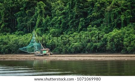 traditional fisherman boat on Mahakam riverbank, Borneo, Indonesia #1071069980