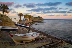 Traditional fishing boats on the beach at sunset at La Isleta del Moro town, Cabo de Gata-Nijar National Park, Almeria province, Andalusia, Spain