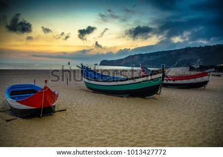 Traditional fishing boats on the sandy beach of Nazare at sunset dusk twilight, Portugal, Atlantic ocean