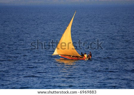 traditional fishing sailing boat out on the ocean with the wind in it's sails
