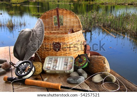 Traditional fly-fishing rod with equipment beside a lake