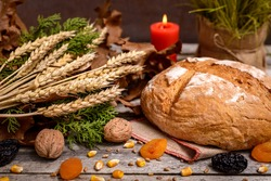 Traditional food for orthodox Christmas eve. Yule log or badnjak, bread, cereals, dried fruits and burning candle on wooden table. Concept celebration orthodox Christmas.