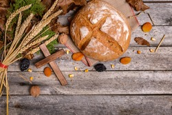 Traditional food for orthodox Christmas eve. Yule log or badnjak, bread, cereals, dried fruits and wooden cross on wooden table. Concept celebration orthodox Christmas.