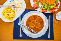Traditional food from Alentejo - cow's tongue in a sauce served with salad, rice, and french fries