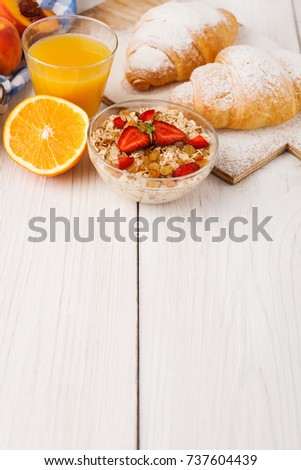 Traditional french breakfast menu . Yogurt with fresh berries, glass of orange juice, muesli and croissants on wooden table, copy space #737604439