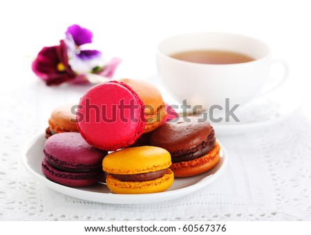 traditional french macaroons with tea on white isolated background