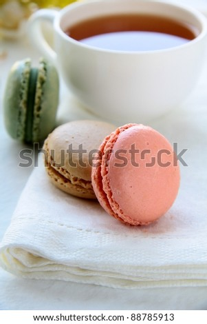 traditional french macrons with tea set on the background