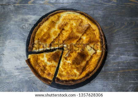 Traditional French Quiche Lorraine pie made of brie with a slice cut, seen from above, on display on a rustic wooden table. It is an iconic dish of Eastern France, a pastry made of flan, brie cheese,