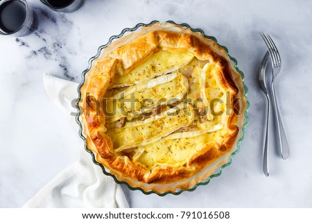Traditional French Quiche Lorraine with Camembert or brie cheese with pears and rosemary on a white marble table. Homemade pie made of puff pastry and two glass of red wine