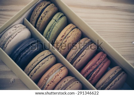 traditional french sweet dessert colorful delicious macarons in a rows in a box on wood background focus on red and green process on retro vintage tone