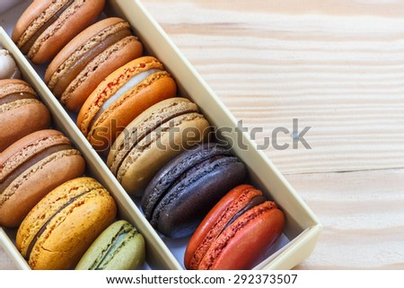 traditional french sweet dessert colorful delicious macarons in a rows in a box on wood background focus on red and green