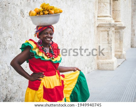 Traditional fresh fruit street vendor aka Palenquera in the Old Town of Cartagena in Cartagena de Indias, Caribbean Coast Region, Colombia.