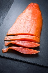 Traditional fresh graved salmon filet offered as closeup on a black board as background with copy space
