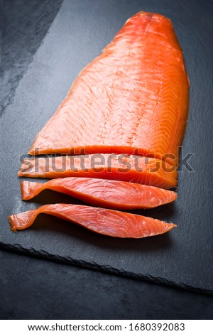 Traditional fresh graved salmon filet offered as closeup on a black board as background with copy space  Сток-фото ©