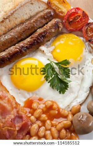 Traditional Full English Breakfast -fried sunny-side-up eggs, sausages, beans, mushrooms and bacon