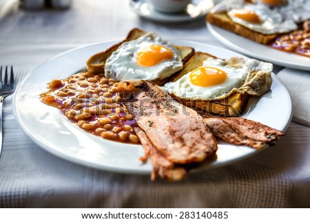 Traditional full english breakfast. Sunny-side-up fried eggs, baked beans, bacon and toast