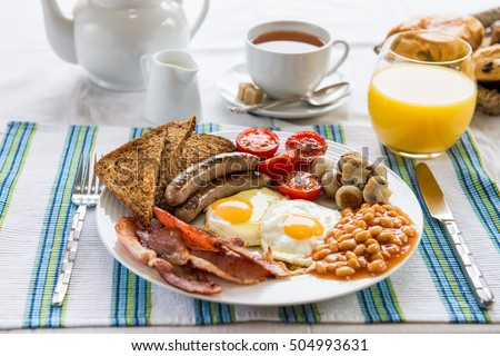 Traditional Full English Breakfast with sunny-side-up fried eggs,  bacon, sausages, beans in tomato sauce, toasts,  fried tomatoes and mushrooms. Also, with Tea, Orange Juice and Puff Pastry.   Stock photo ©