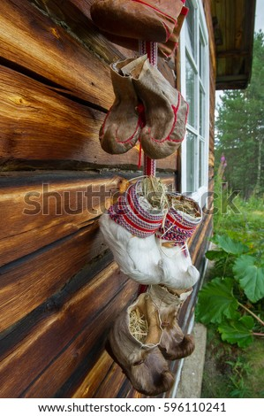 traditional fur boots of sami people hanging on a wall #596110241