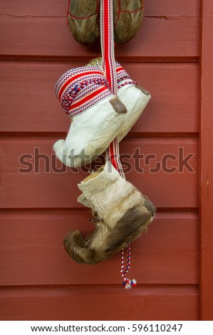 traditional fur boots of sami people hanging on a wall #596110247