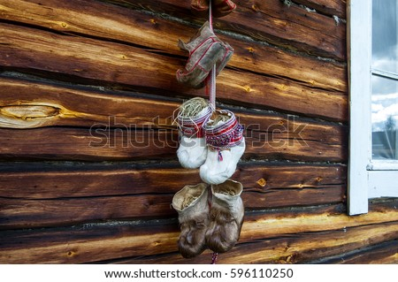 traditional fur boots of sami people hanging on a wall #596110250