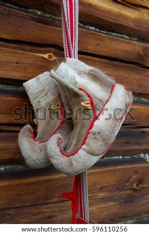 traditional fur boots of sami people hanging on a wall #596110256