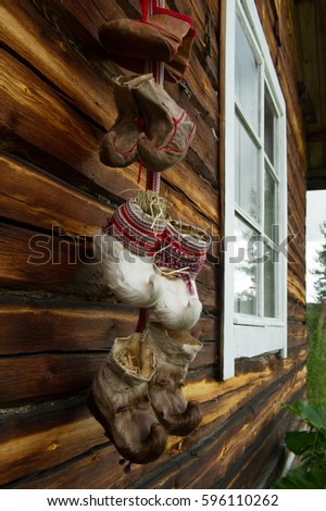 traditional fur boots of sami people hanging on a wall #596110262