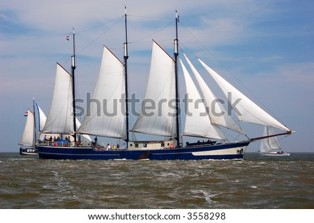 Traditional gaffrigged 3 masted dutch sailing barge, with other boats in the background.