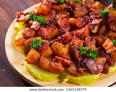 Traditional Galician fair dish of braised pig snouts served with sliced cooked potatoes, smoked paprika and olive oil (Morro a la gallega)