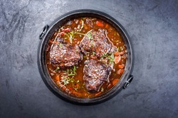 Traditional German braised beef cheeks in brown red wine sauce with carrots and onion offered as top view in a modern design stewpot on an old rustic board