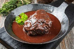 Traditional German braised beef cheeks in brown red wine sauce with herbs as closeup in a wrought-iron skillet on an old burnt board