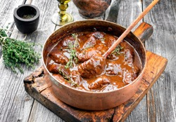 Traditional German braised pork cheeks in brown red wine sauce with mushroom and onions as closeup in a casserole
