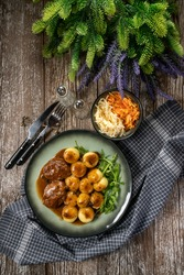 Traditional German braised pork cheeks in brown sauce with mushroom served with silesian dumplings.