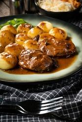 Traditional German braised pork cheeks in brown sauce with mushroom served with silesian dumplings.