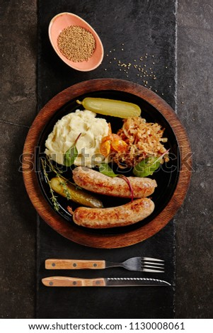Traditional German Sausages with Mashed Potato and Sauerkraut. Wurst or Bratwurst with Fermented Cabbage, Pickled Cucumbers, and Spices in Rustic Wood Bowl on Natural Black Stone Background Top View Сток-фото ©