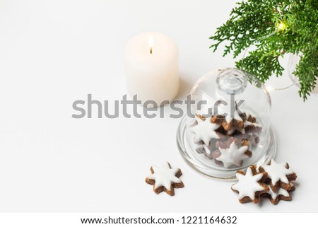Traditional German star shaped cinnamon cookies with icing in cloche dome bell glass jar on white table. Lit candle juniper with golden garland lights. Magic festive atmosphere