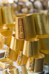 Traditional gold bracelets, close-up vertical details. Turkish work wicker gold bracelet showcase. Trabzon gold wicker bracelet. Turkey, the Grand Bazaar. Gold, gems, precious gift, wedding, wealth.