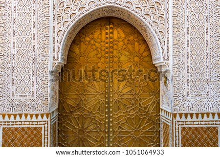 Traditional golden Moroccan door with floral arabesque decoration