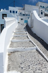 Traditional Greek cobblestone walkway with white washed walls leading up to a group of homes on the island of Santorini Greece.