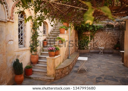 Traditional greek courtyard on the street with flowers and stairway - Anafiotika, Plaka, Athens, Greece #1347993680